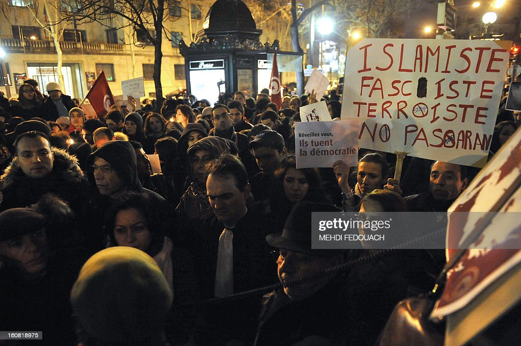 A protester holds a placard reading 'wake up, they're killng Democracy' during a demonstration on February 6, 2013 held outside the Tunisian embassy in Paris against the killing today of prominent Tunisian opposition leader Chokri Belaid. Furious protesters on February 6 erected barricades in central Tunis and hurled rocks at police who tried to disperse them with tear gas in new clashes after the assassination of a prominent opposition figure.