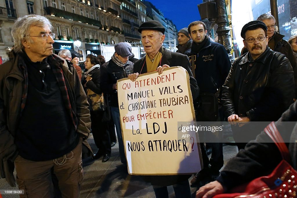 A protester holds a placard reading 'What (French Interior Minister) Manuel Valls and (French Jusctice Minister) Christiane Taubira are waiting for to prevent LDJ from assaulting us?' during a demonstration with about 120 members of the 'Indigenous of the Republic's Party' (PIR), on November 8, 2012 in front of France's Justice Ministry in Paris, to claim the dissolution of the Jewish Defence League (LDJ), as they accuse this jewish organisation of far-right attacks on pro-Palestinian supporters. On October 25, the LDJ uploaded on Youtube website a video showing PIR's spokeswoman Houria Bouteldja and pro-Palestinian militants Olivia Zemor and Jacob Cohen, sprayed with red paint after being assaulted by LDJ members.