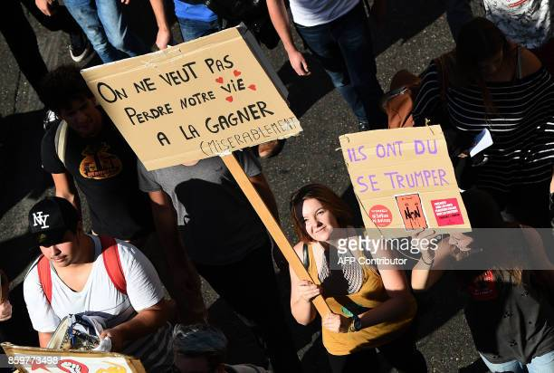 A protester holds a placard reading 'You don't want to lose our lives by making a living ' during a demonstration on October 10 in Marseille...