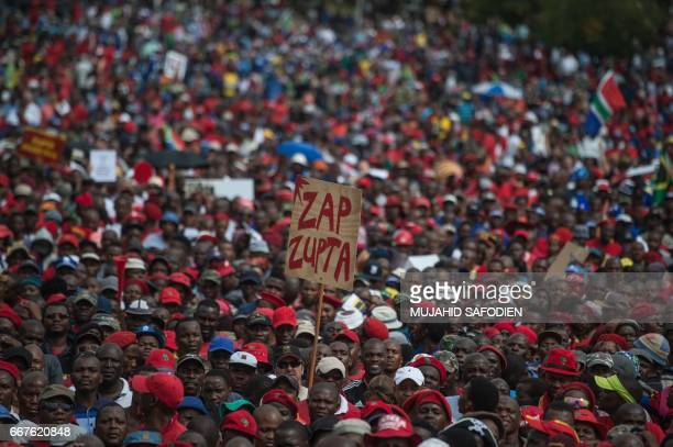 TOPSHOT A protester holds a placard reading 'Zap Zupta' refering to Zuma and the Gupta Family as South African demonstrators from various political...