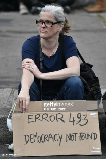 A protester holds a placard refering to the constitution's controversial Article 493 allowing the government to bypass parliament during a...