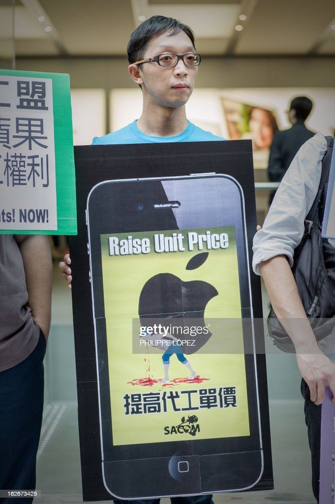 A protester holds a placard shaped as an iPhone as he and others protest against working conditions at Apple suppliers in China, in front of an Apple store in Hong Kong on February 26, 2013. Recent investigations in 2012 by New York-based China Labor Watch found that working conditions in factories suppliers to Apple in southern and eastern China uncovered violations of workers' rights, including excessive overtime and hazardous work conditions. AFP PHOTO / Philippe Lopez