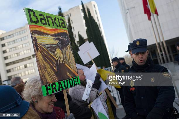 A protester holds a placard showing a copy of the painting by artist Edvard Munch called 'The Scream' outside a Madrid court where exBankia president...