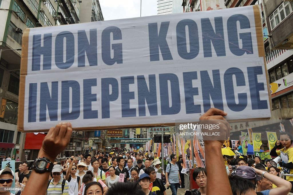 A protester holds a placard which reads 'Hong Kong Independence' during a pro-democracy rally in Hong Kong on July 1, 2016, traditionally a day of protest which also marks the anniversary of the handover from Britain to China in 1997. Protesters took to the streets of Hong Kong on July 1 to mark the anniversary of the city's handover from Britain to China, with pro-independence groups rallying for the first time amid fears Beijing is tightening its grip. / AFP / ANTHONY