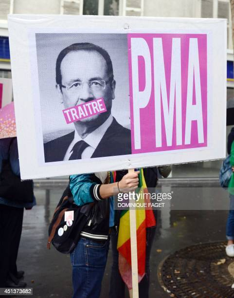 A protester holds a placard with the picture of French President Francois Hollande and the word 'traitor' next to the acronym PMA during the lesbian...