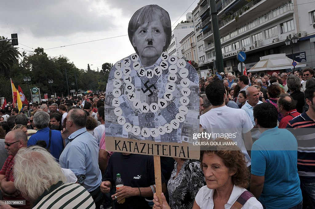 A protester holds a plackard of German Chancellor Angela Merkel featuring a Hitler moustache near the Greek parliament in Athens during a demonstration against the vist of the German Chancellor Angela Merkel on October 9, 2012. Athens went into security lockdown for a landmark visit by German Chancellor Angela Merkel, an austerity hate figure in Greece whose arrival will be greeted by union and opposition party protests. Thousands of police fanned out across the capital, creating a large safety zone for Merkel's meetings with Prime Minister Antonis Samaras and President Carolos Papoulias in which all gatherings and protests have been banned.