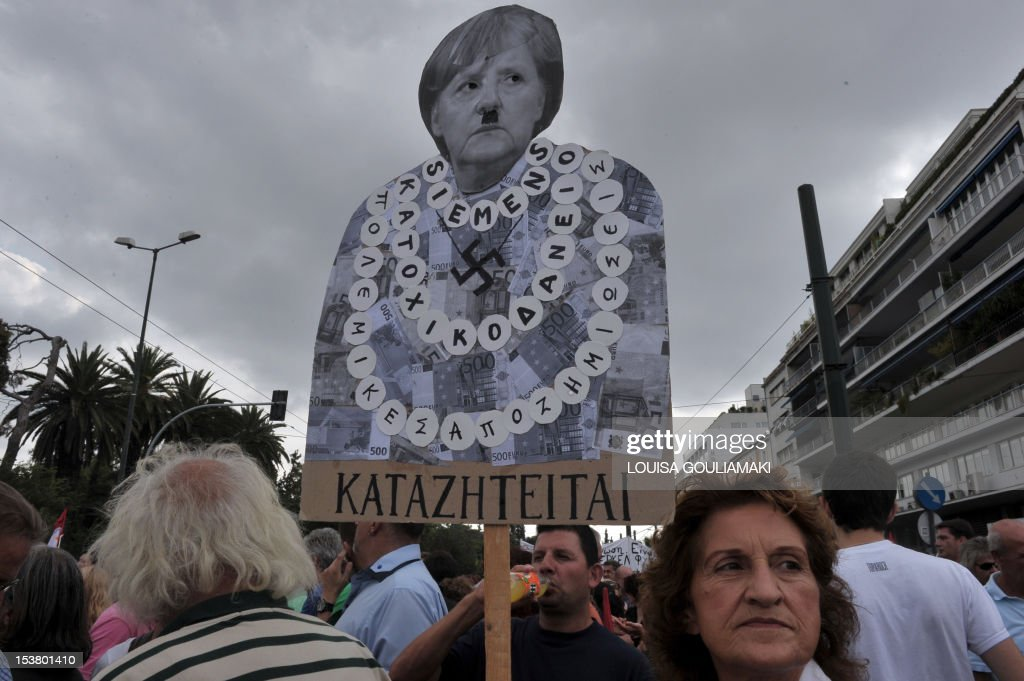 A protester holds a plackard of German Chancellor Angela Merkel featuring a Hitler moustache near the Greek parliament in Athens during a demonstration against the vist of the German Chancellor Angela Merkel on October 9, 2012. Athens went into security lockdown for a landmark visit by German Chancellor Angela Merkel, an austerity hate figure in Greece whose arrival will be greeted by union and opposition party protests. Thousands of police fanned out across the capital, creating a large safety zone for Merkel's meetings with Prime Minister Antonis Samaras and President Carolos Papoulias in which all gatherings and protests have been banned. AFP PHOTO /LOUISA GOULIAMAKI