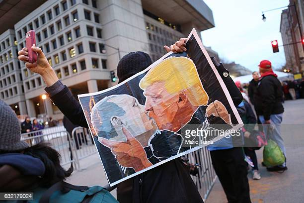 A protester holds a poster depicting Presidentelect Donald Trump and Russian President Vladimir Putin kissing during an antiTrump demonstration on...