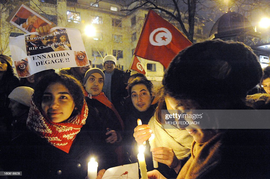A protester holds a poster reading 'Tunisia in mourning, RIP Chokri Belaid, Ennahdha get out' as others hold candles during a demonstration on February 6, 2013 held outside the Tunisian embassy in Paris against the killing today of prominent Tunisian opposition leader Chokri Belaid. Furious protesters on February 6 erected barricades in central Tunis and hurled rocks at police who tried to disperse them with tear gas in new clashes after the assassination of a prominent opposition figure. AFP PHOTO / MEHDI FEDOUACH