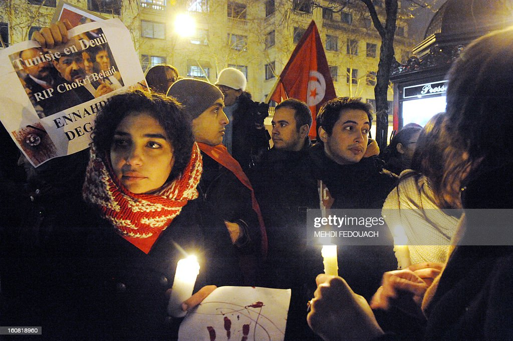 A protester holds a poster reading 'Tunisia in mourning, RIP Chokri Belaid, Ennahdha get out' as others hold candles during a demonstration on February 6, 2013 held outside the Tunisian embassy in Paris against the killing today of prominent Tunisian opposition leader Chokri Belaid. Furious protesters on February 6 erected barricades in central Tunis and hurled rocks at police who tried to disperse them with tear gas in new clashes after the assassination of a prominent opposition figure.