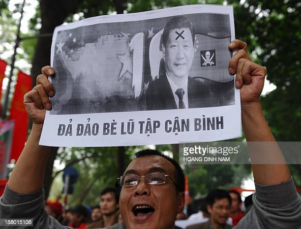 A protester holds a poster with portrait of newly elected Chinese president Xi Jinping reading 'Down with Xi Jinping's gang' during an antiChina...