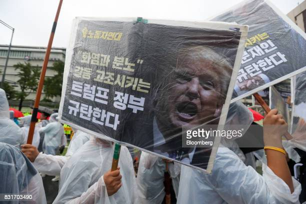 A protester holds a protest banner featuring a photograph of US president Donald Trump in front of US embassy during a rally against the deployment...
