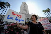 A protester holds a sign after a march to Los Angeles City Hall during the 'Occupy Los Angeles' demonstration in solidarity with the ongoing 'Occupy...