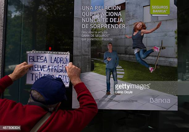 A protester holds a sign against a branch of Spanish bank Bankia near Madrid's High Court where Rodrigo Rato former chairman of rescued bank Bankia...