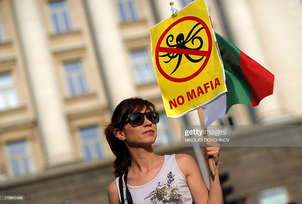 A protester holds a sign and a flag of Bulgaria during an anti-government protest on June 20, 2013 in front of the government's headquarters in the center of Sofia. Bulgaria's president urged political leaders on June 20 to heed the demands of thousands of protestors who have rallied for the past six days against the political establishment in the EU's poorest country. Between 7,000 and 10,000 protestors have rallied in Sofia every evening since last Friday, just four months after demonstrations prompted the resignation of the last government and three weeks into a new administration.