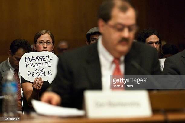 A protester holds a sign behind Don L Blankenship chairman and CEO of Massey Energy Co during a Senate Appropriations Subcommittee on Labor Health...