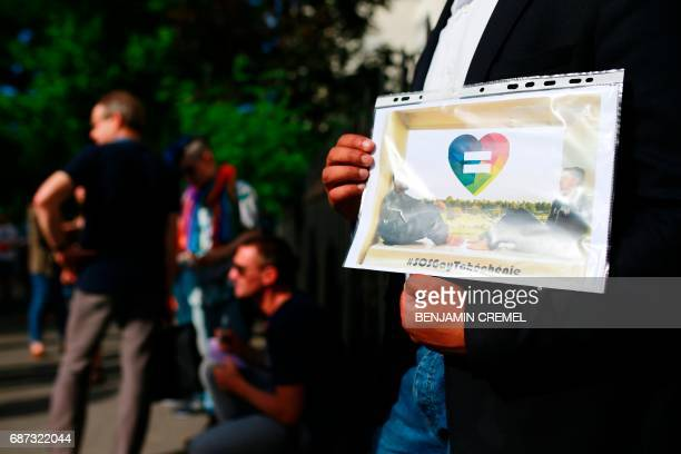 A protester holds a sign during a demonstration in support of gay rights and against homophobia in Chechnya in front of the Russian Embassy in Paris...