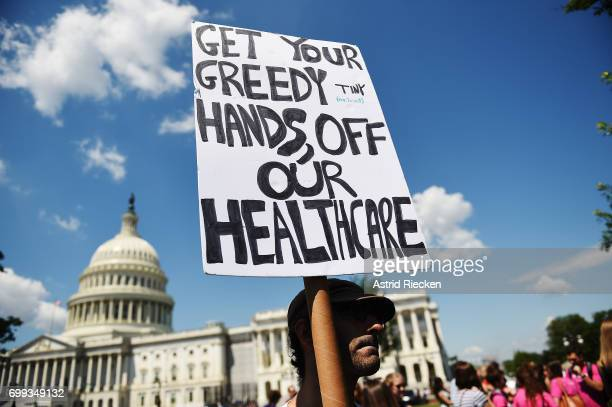 A protester holds a sign during a demonstration of Democratic Senators to oppose the repeal of the Affordable Care Act and its replacement on Capitol...