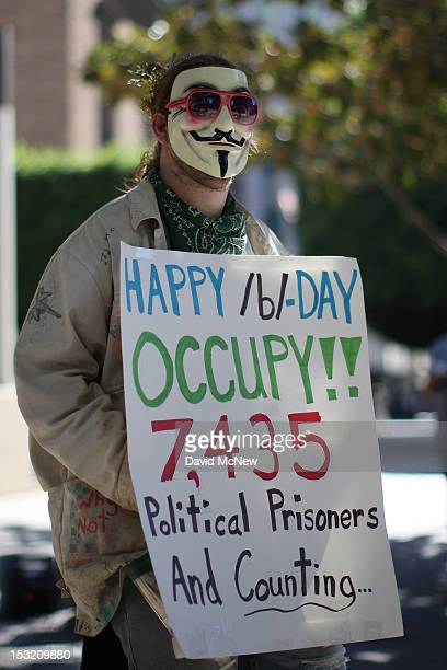 A protester holds a sign during a rally in the downtown financial district to mark the oneyear anniversary of the Occupy movement on October 1 2012...