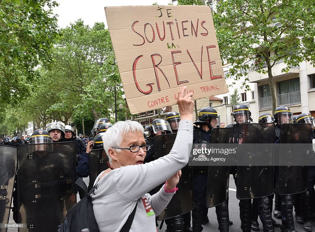 A protester holds a sign next to French police as General Confederation of Labour (CGT) commences their 8th widespread protests all around the France for protesting French government's labor law reform in Paris, France on May 26, 2016.