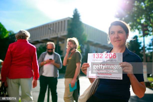 A protester holds a sign reading 'Emmanuel Macron act for homosexuals in Chechnya' during a demonstration in support of gay rights and against...