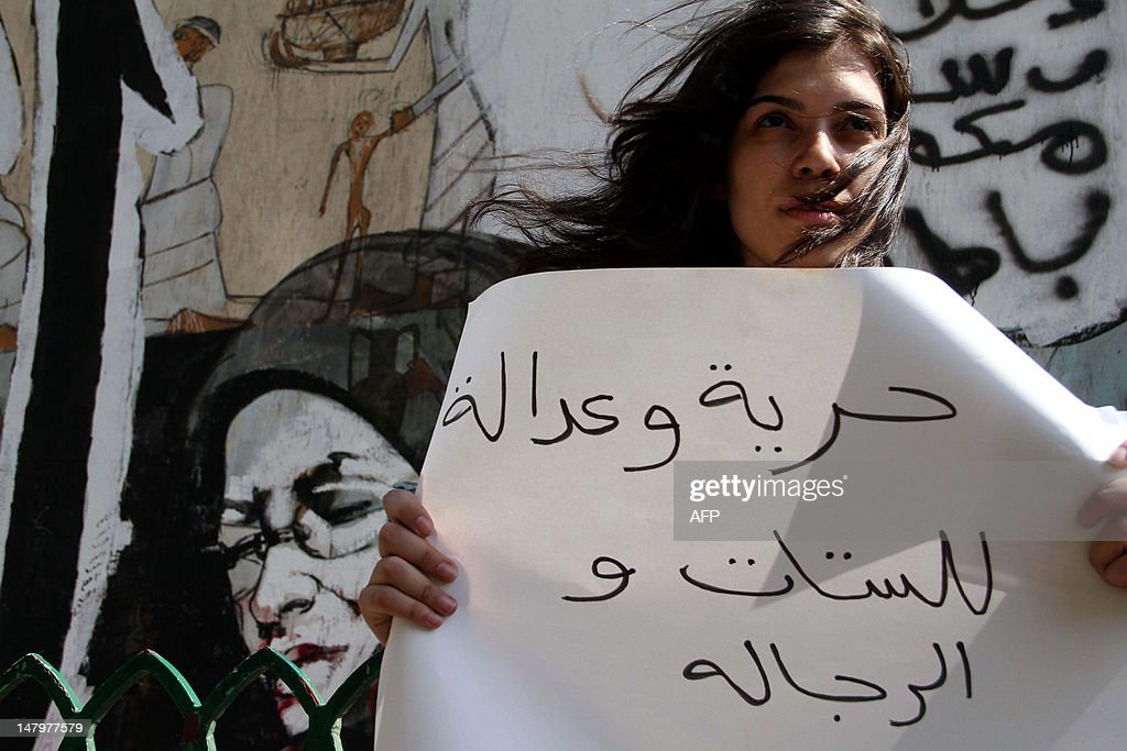 A protester holds a sign reading 'Freedom and justice for women and men' during a demonstration in Cairo against sexual harassment in Egypt on July 6, 2012. Escorted by volunteers in charge of their protection, women march towards Tahrir Square to protest against sexual harassment in the landmark square, symbol of Egypt's revolution that has become a danger zone for women.