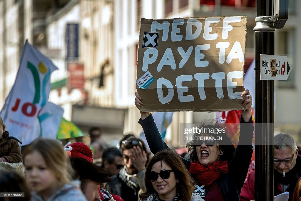 A protester holds a sign reading 'MEDEF (Movement of the Enterprises of France), pay your debt' as people march in the streets of Lille during a May Day rally on May 1, 2016. / AFP / PHILIPPE