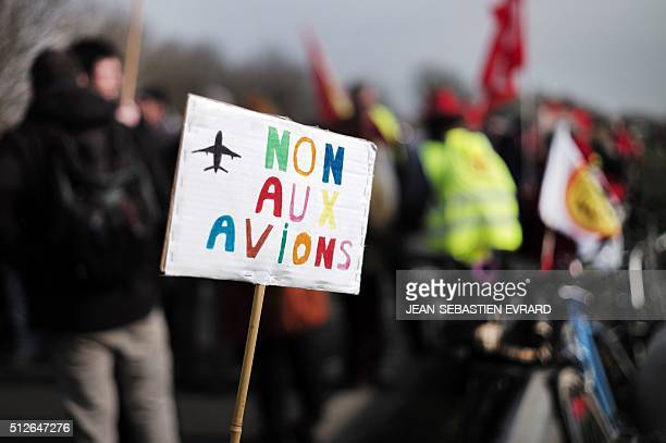 A protester holds a sign reading 'No to planes' as demonstrators block a highway in Le TempledeBretagne during a protest against a controversial...