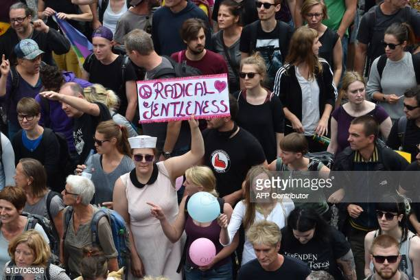 A protester holds a sign reading 'Radical Gentleness' during the 'solidarity without borders instead of G20' demonstration on July 8 2017 in Hamburg...