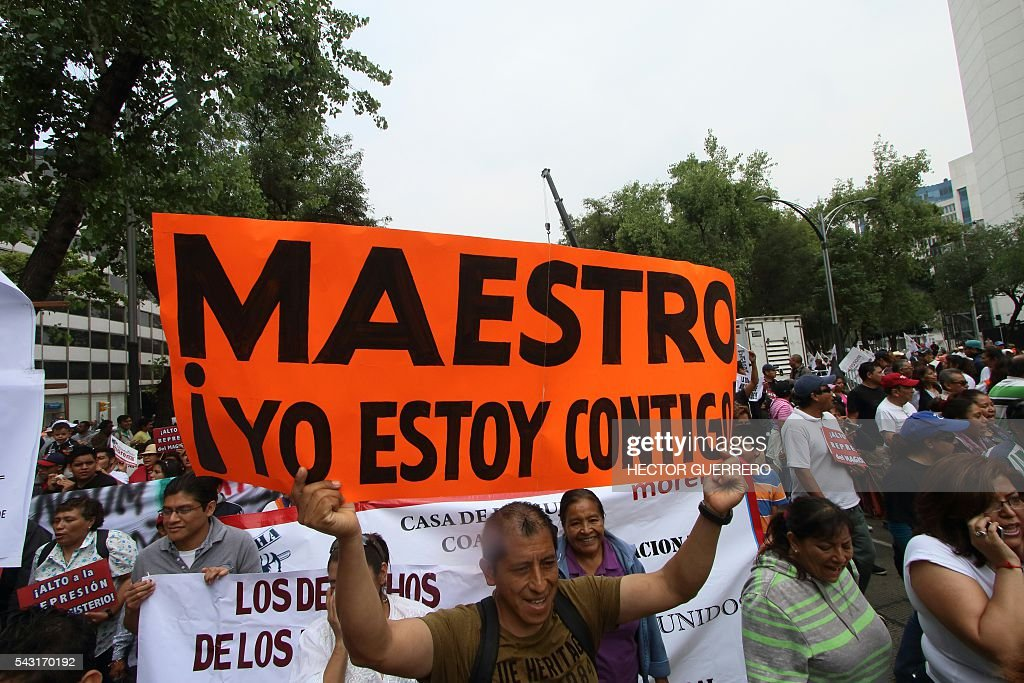 A protester holds a sign reading 'Teacher, I am with you!' as supporters of Mexican leader of the National Regeneration Movement, Andres Manuel Lopez Obrador, demonstrate in support of the National Coordination of Education Workers (CNTE) teachers' union, and against an education reform launhced by the government along Reforma Avenue in Mexico City on June 26, 2016. / AFP / HECTOR