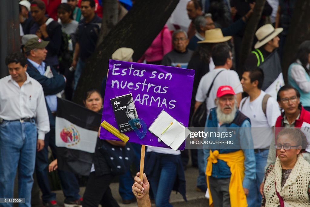 A protester holds a sign reading 'These are our weapons' as supporters of Mexican leader of the National Regeneration Movement, Andres Manuel Lopez Obrador, demonstrate in support of the National Coordination of Education Workers (CNTE) teachers' union, and against an education reform launhced by the government along Reforma Avenue in Mexico City on June 26, 2016. / AFP / Hector GUERRERO