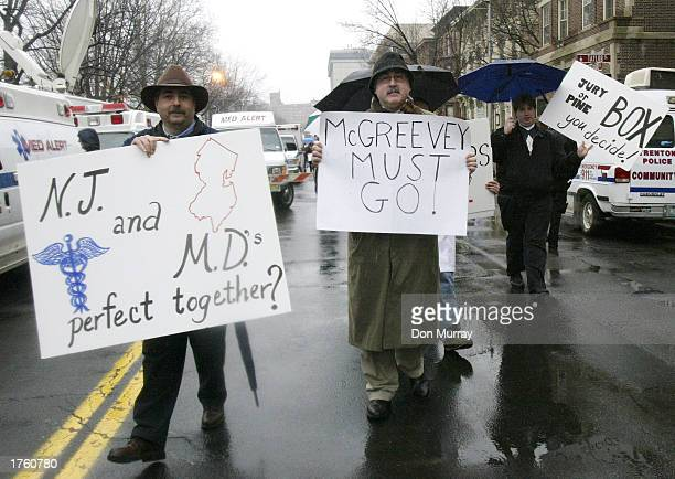 A protester holds a sign that reads 'McGreevey Must Go' at a rally at the New Jersey Capitol Complex February 4 2003 in Trenton New Jersey About 3000...