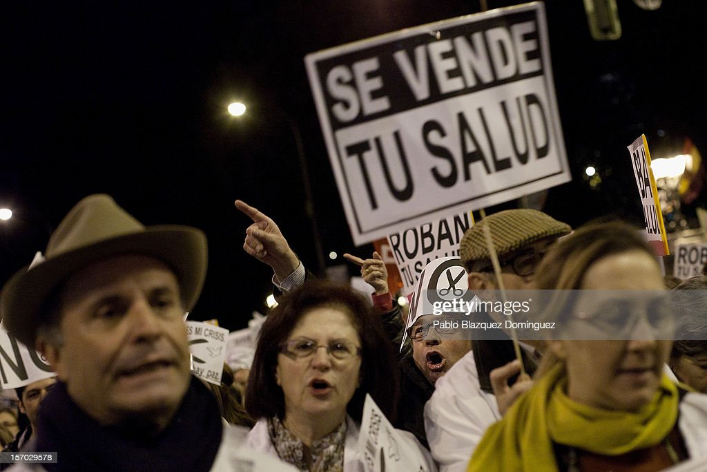 A protester holds a sign that reads 'Your health for sale' amid other health workers during a demonstration held on the second day of a two day general strike on November 27, 2012 in Madrid, Spain. For the first time all trade unions call for a 48 hours health workers general strike in Madrid Region after Regional Government anounced severe cuts and privatization of Medical Centers.