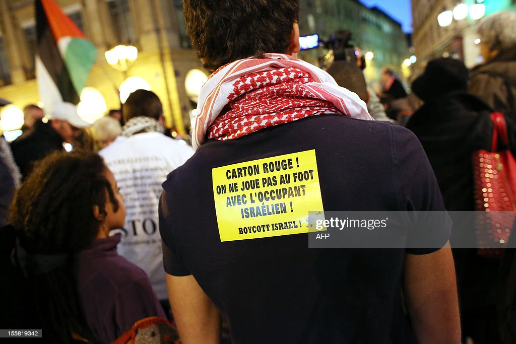 A protester holds a sticker reading 'Red Card ! We do not play football with the Israeli occupant! Boycott Israel' during a demonstration with about 120 members of the 'Indigenous of the Republic's Party' (PIR), on November 8, 2012 in front of France's Justice Ministry in Paris, to claim the dissolution of the Jewish Defence League (LDJ), as they accuse this jewish organisation of far-right attacks on pro-Palestinian supporters. On October 25, the LDJ uploaded on Youtube website a video showing PIR's spokeswoman Houria Bouteldja and pro-Palestinian militants Olivia Zemor and Jacob Cohen, sprayed with red paint after being assaulted by LDJ members. AFP PHOTO / THOMAS SAMSON