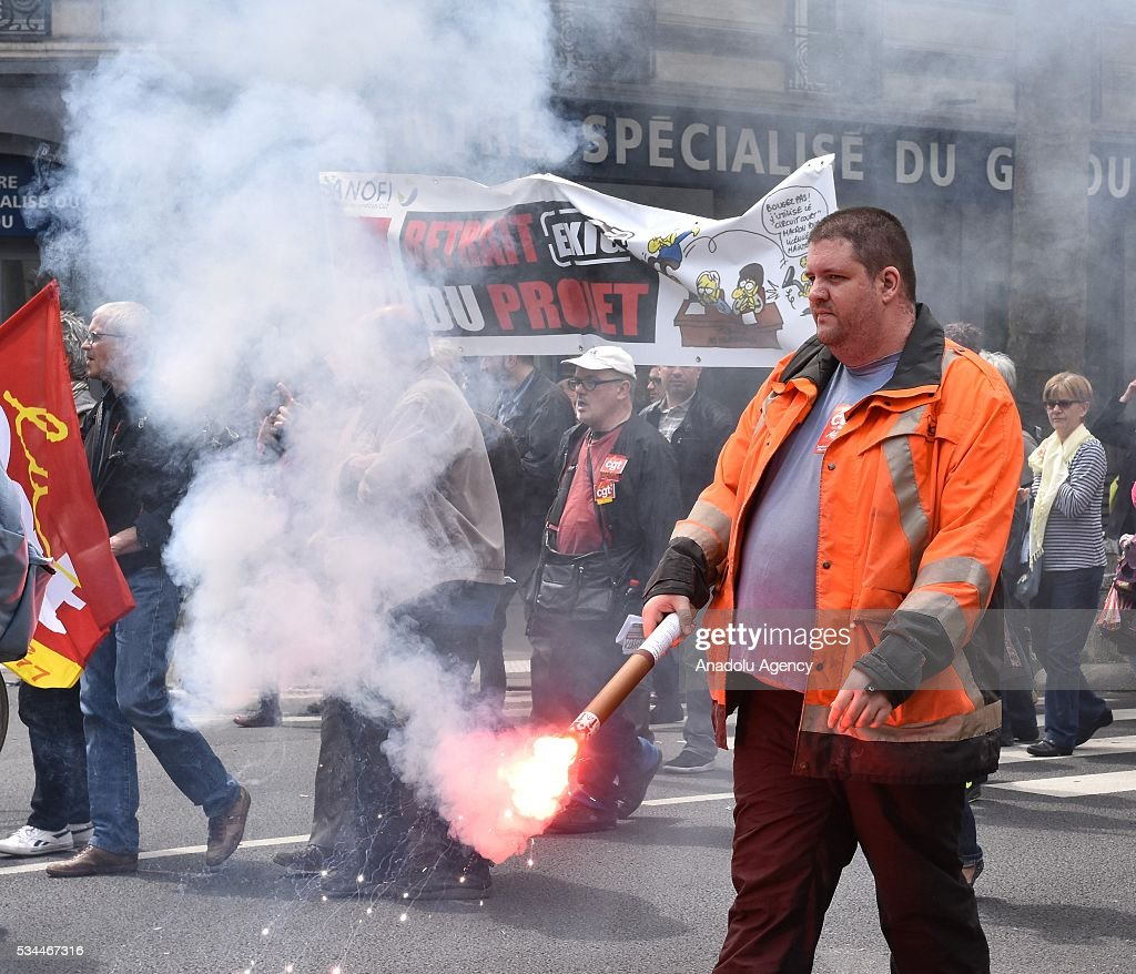 A protester holds a torch as General Confederation of Labour (CGT) commences their 8th widespread protests all around the France for protesting French government's labor law reform in Paris, France on May 26, 2016.