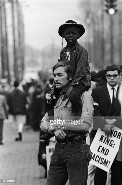 A protester holds a young Black boy on his shoulders during the Memphis March demonstration backing the demands of Memphis' striking garbage workers...