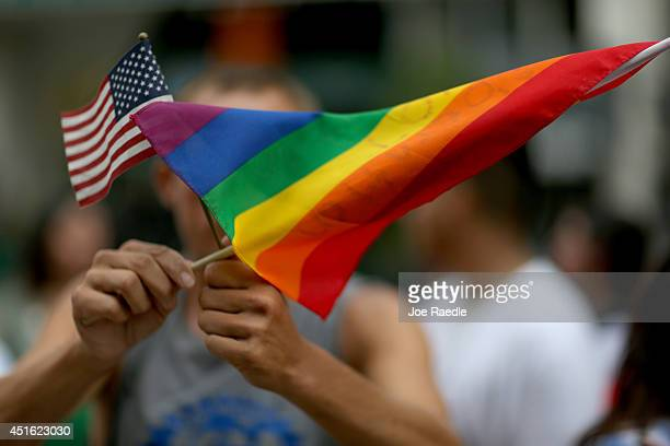 A protester holds an American flag and rainbow flag in front of the MiamiDade Courthouse to show his support of the LGBTQ couples inside the...