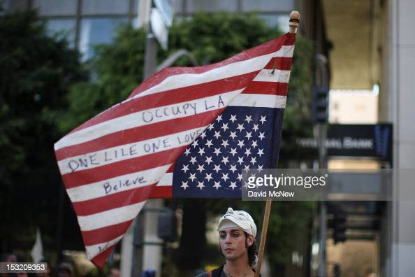 A protester holds an American flag during rally in the downtown financial district to mark the oneyear anniversary of the Occupy movement on October...