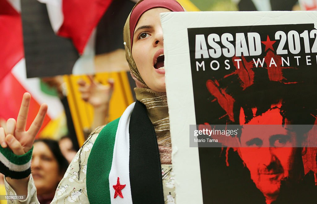 A protester holds an anti-Bashar Assad, President of Syria, sign at a rally of groups opposing Iranian President Ahmadinejad's speech at the United Nations General Assembly on September 26, 2012 in New York City. Politicians including former New York Mayor Rudolph Giuliani, former House Speaker Newt Gingrich, former Homeland Security Secretary Tom Ridge, former New Mexico Governor Bill Richardson and former U.N Ambassador John Bolton spoke at the pro-democracy rally which also included Syrian pro-democracy protesters.