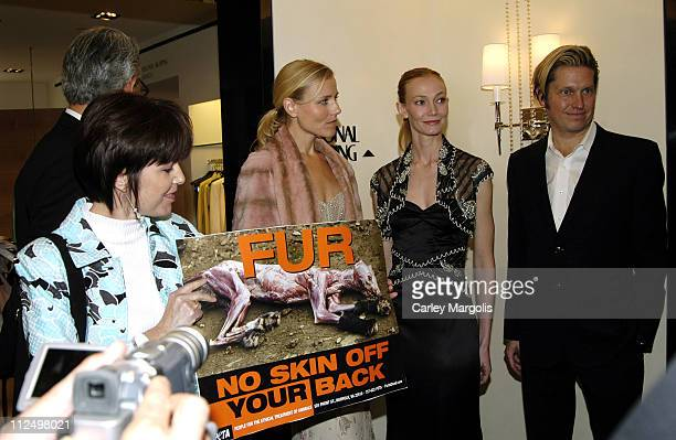A PETA protester holds an antifur poster while Mark Badgley leaves the room and James Mischka and models wearing their creations look on
