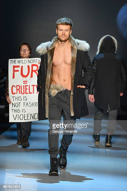 A protester holds an antifur sign on the runway during the show for The Wild North fall 2015 collection during World MasterCard Fashion Week Fall...