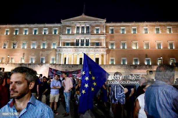 A protester holds an EU flag as people gather in front of the Greek parliament in Athens on June 20 2017 during a demonstration against the country's...