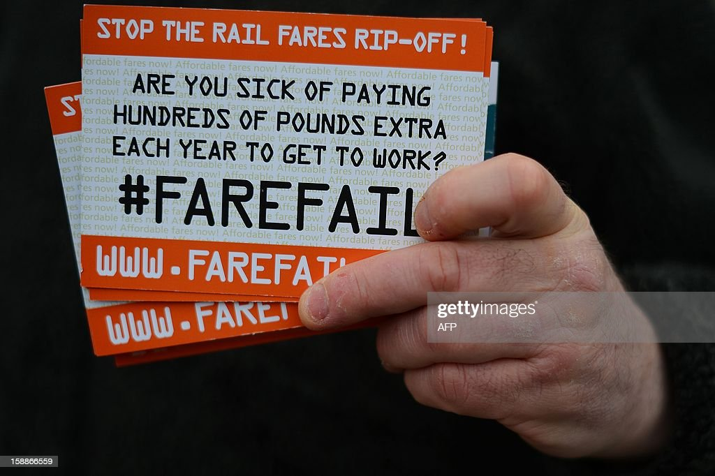 A protester holds flyers during a demonstration against a hike in rail fares at Kings Cross station in central London on January 2, 2013. Rail commuters were hit with an average 4.2% fare rise as an increase in season ticket rates announced in August 2012 came into effect.