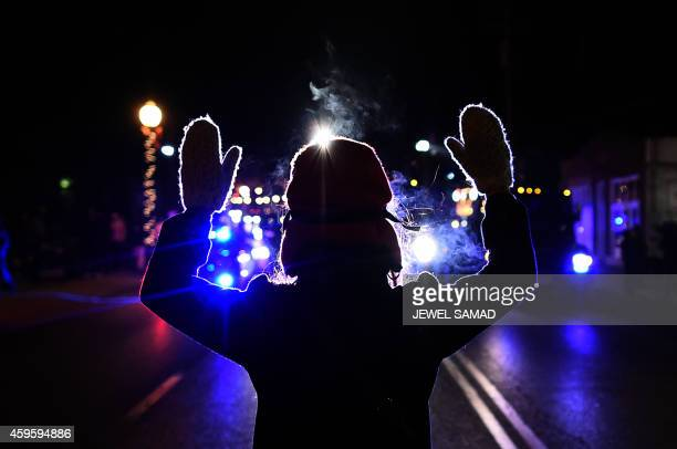 A protester holds her hands up in front of a police car in Ferguson Missouri on November 25 2014 during demonstrations a day after violent protests...