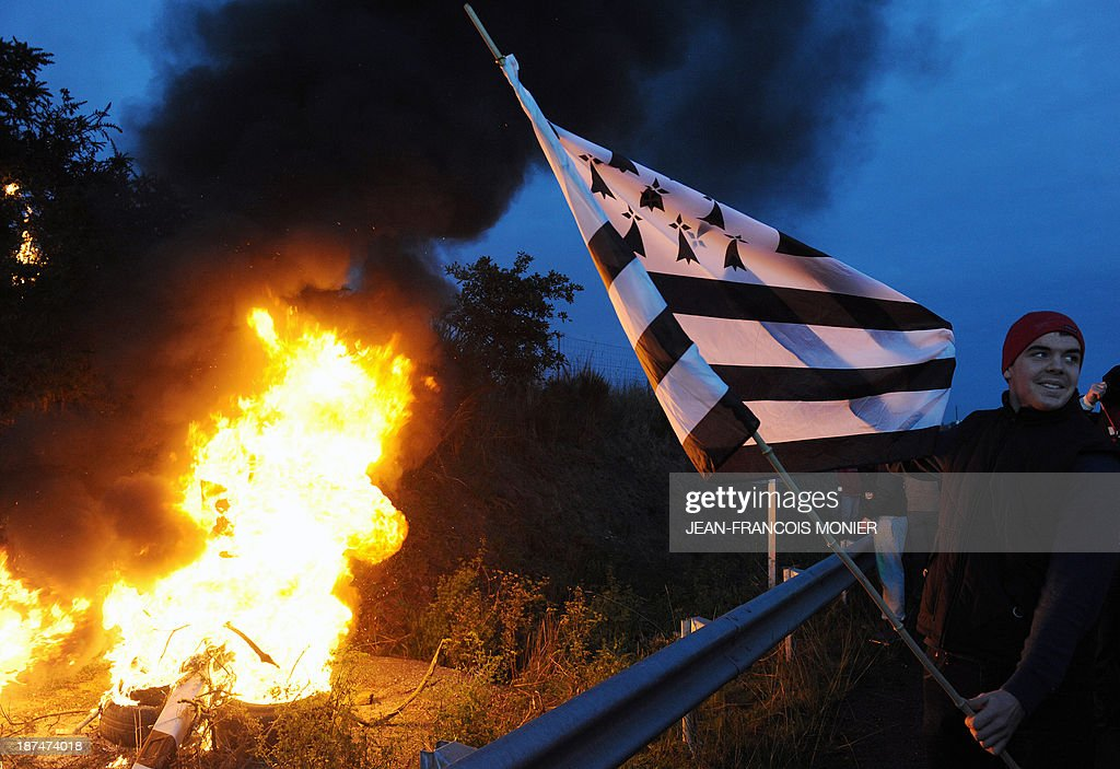 A protester holds of flag of the French western region Brittany after a radar was set to fire near an 'Ecotax' control portal during a demonstration against jobcuts and against the government's controversial environmental tax on heavy goods vehicles in Jugon-les-Lacs, western France, on November 9, 2013. The ecotax, aimed at encouraging environmentally friendly commercial transport, imposes new levies on French and foreign vehicles transporting commercial goods weighing over 3.5 tonnes but its implementation has repeatedly been put off.