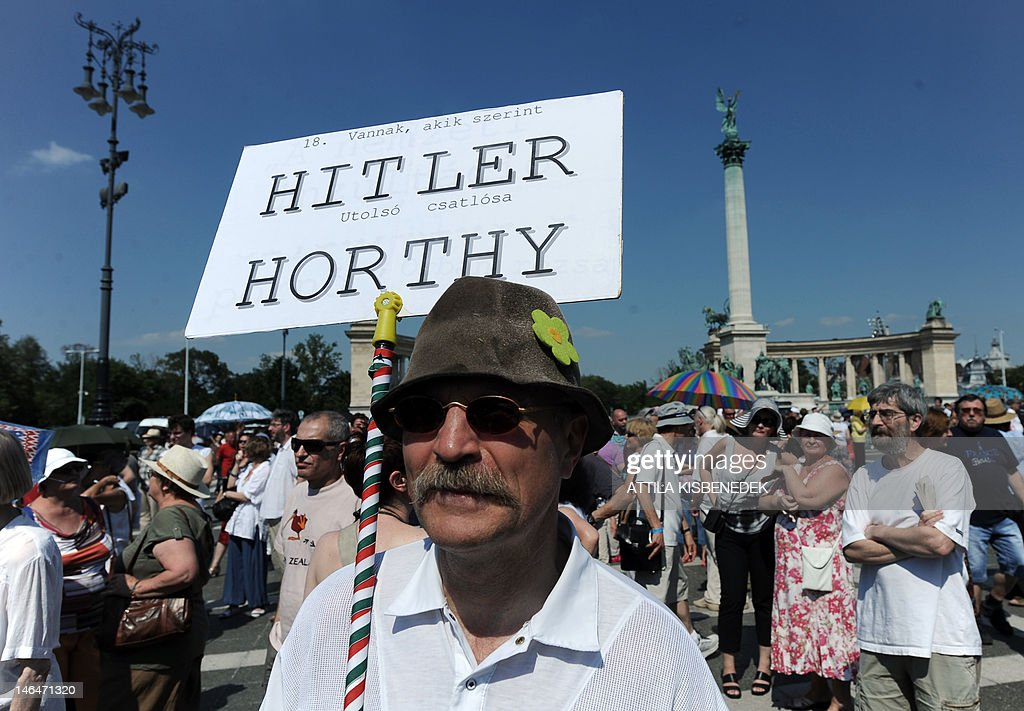 A protester holds on June 17, 2012 a placard comparing Hungarian World War II-era leader Miklos Horthy with German dictator Adolf Hitler and reading: 'There are some who argue that Hitler's last shield bearer was Horthy,' on Heroes square in Budapest. A bust statue of Horthy was unveiled on June 16 in the historical settlement of Csokako. Horthy's defenders say he brought stability to the country during hard times after World War I, when Hungary lost two-thirds of its territory to its neighbors. His critics condemn the leader, in power from 1920 to 1944, for backing anti-Semitic legislation and for deporting more tha 500,000 Jews and Roma to camps during his alliance with Nazi Germany.