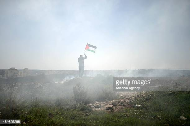 A protester holds Palestinian Flag during a protest against the construction of Jewish settlement housing and the separation wall in the village of...