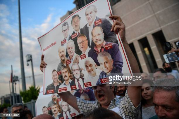 A protester holds pictures of Cumhuriyet journalists during a demonstration in Istanbul on July 28 2017 after a Turkish court ordered the release of...
