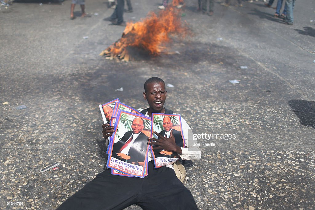 A protester holds pictures of former Haitian President <a gi-track='captionPersonalityLinkClicked' href=/galleries/search?phrase=Jean-Bertrand+Aristide&family=editorial&specificpeople=176717 ng-click='$event.stopPropagation()'>Jean-Bertrand Aristide</a> as demonstrators make their voices heard in opposition to Haitian President Michel Martelly who is locked in a stalemate over parlimentary elections on January 11, 2015 in Port-au-Prince, Haiti. The day before the anniversary of the magnitude 7.0 earthquake that struck just before 5 p.m. on Jan. 12, 2010, destroying buildings and killing as many as 316,000 people, protesters are asking the government to hold elections and for the president to step down after the elections have been delayed for over three years.