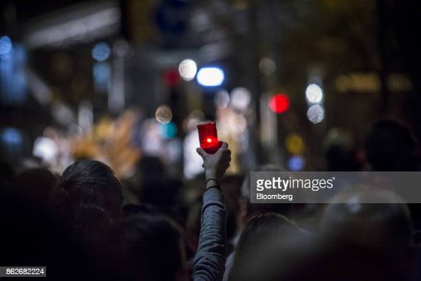 A protester holds up a candle during a vigil to demand the release of imprisoned seperatist leaders Jordi Sanchez head of the Catalan National...